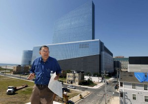 "Charlie Birnbaum stands on his roof with the closed Revel Casino Hotel in the background. ""I don't think I'm in anybody's way whatsoever,"" he said. (MEL EVANS / AP, File)"